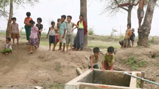Dos niños miran un pozo mientras otros hacen cola para recoger comida en Rangún. (EFE/Epa Photo)