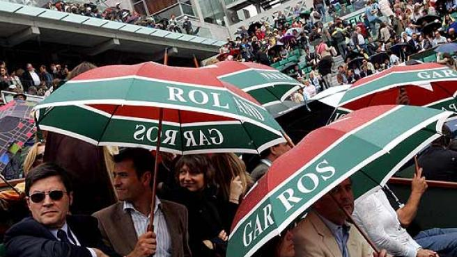 Los espectadores del Roland Garros bajo la lluvia. (Efe)