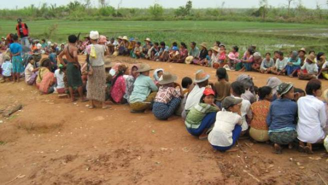Un grupo de supervivientes del ciclón 'Nargis', sentados junto a una carretera. (REUTERS/Stringer)
