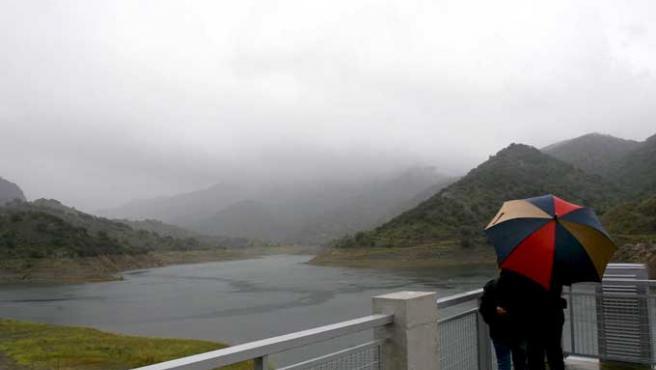 Una pareja observa el pantano de Siurana bajo la lluvia, que da uun respiro a la sequía en Cataluña (EFE / Jaume Sellart)