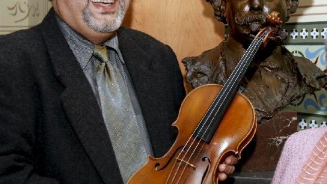 El luthier Haliti sostiene el violín que va a restaurar. EFE