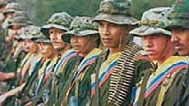 Los fallecidos 'Tirofijo' (izq.) y 'Raúl Reyes', junto a una guerrilla de las FARC. (ARCHIVO)