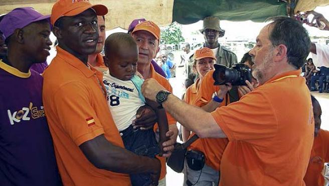 Arouna Koné (i), uno de los jugadores más populares de Costa de Marfil, con un niño en brazos en su barriada natal de Abobo. (Efe)