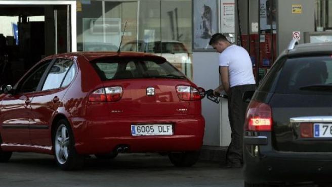 Un joven llena el depósito de su coche.