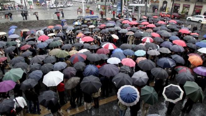 Cientos de personas, en la concentración de Bilbao, bajo los paraguas.