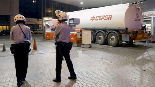 Los Mossos d'Esquadra custodian un camión cisterna que descarga en una gasolinera. (EFE)