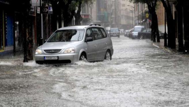 Un vehículo circula por una de las calles de Albacete, inundadas por la lluvia.