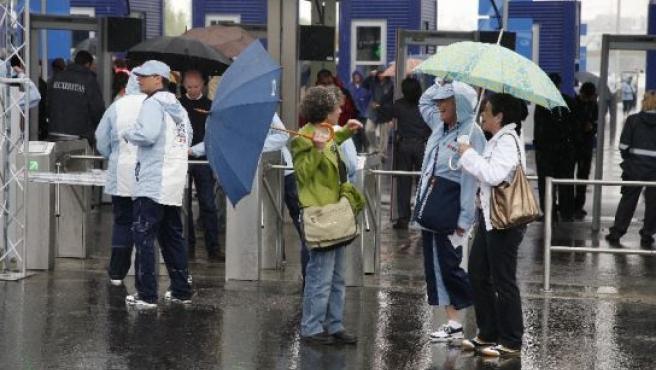 Varios visitantes sufren la lluvia que cayó el martes en el ensayo general de la Expo.