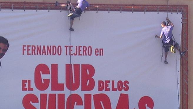 Dos obreros colgados de una fachada de un edificio de la plaza de Callao intentan colocar un cartel.