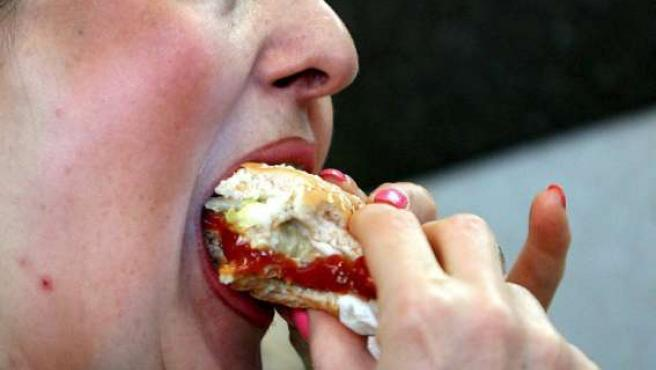 Una mujer saborea una hamburguesa.