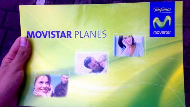 Un ciudadano sostiene un folleto con planes de precios de Movistar.