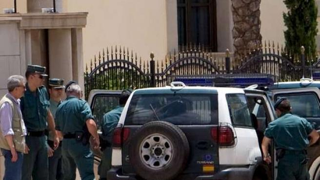 Varios agentes acompañan a un detenido tras el registro de la vivienda del presunto cabecilla de un clan de la mafia rusa.(EFE)