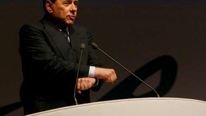 El primer ministrio italiano, Silvio Berlusconi, cruza sus manos como si las tuviese esposadas durante su intervención ante un grupo de empresarios (EFE).