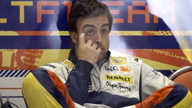 Fernando Alonso descansa en el box de Renault en Silverstone, tras los entrenamientos oficiales. (EFE)