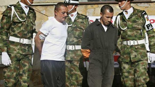 Miembros de la Policía Militar escoltan a los integrantes de las FARC identificados como Gerardo Aguilar Ramírez, alias 'Cesar' y Alexander Farfán, alias 'Gafas'. (EFE)
