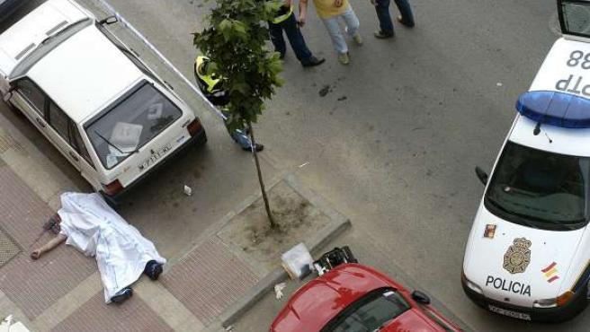 El cadáver de un hombre, en la acera, tras intentar atracar un banco en Parla y ser reducido por la Policía. (ARCHIVO)