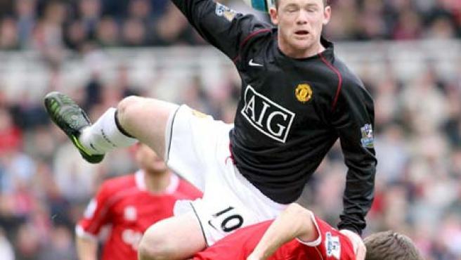 El inglés Rooney lucha por un balón aéreo durante un partido.