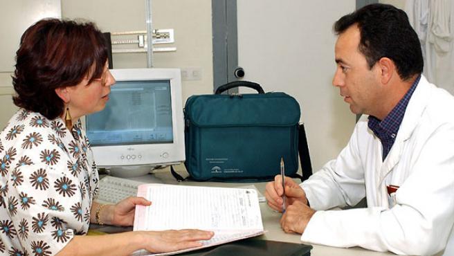 Un médico atiende a una paciente en su consulta.