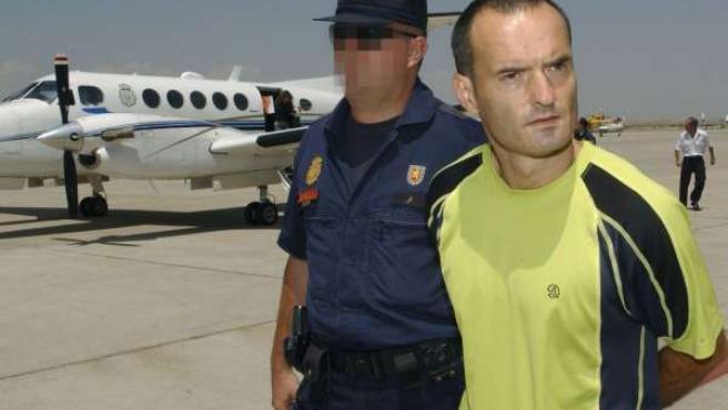 El ex jefe militar de ETA, Juan Antonio Olarra Guridi, es conducido por un policía a su llegada a España.