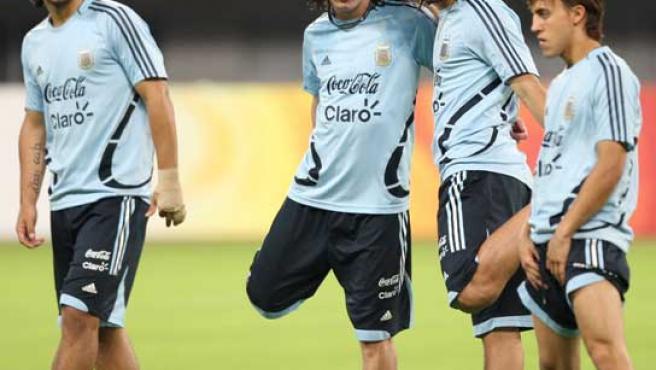 El delantero argentino Leo Messi (centro) realizando ejercicios de estiramiento junto a compañero Banega.
