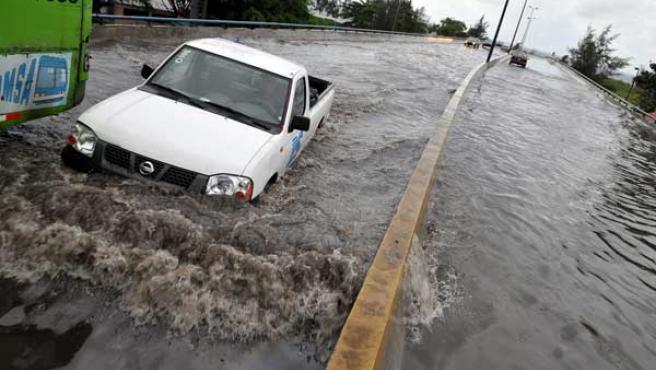 Varios vehículos circulan por una avenida inundada en Santo Domingo (República Dominicana). (EFE)