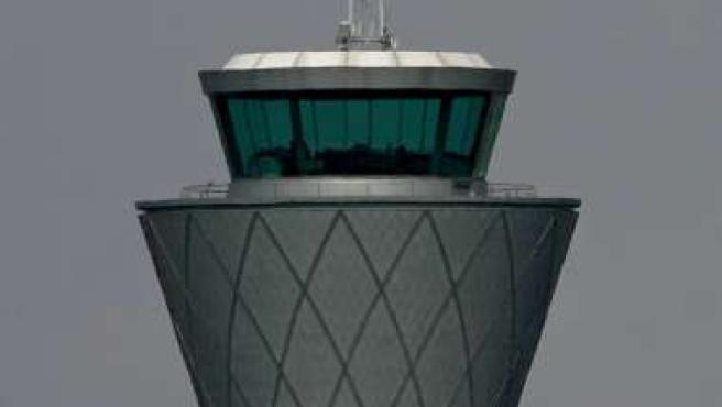 Un avión sobrevuela la torre de control del aeropuerto de BAA, en Edimburgo (Escocia). REUTERS/DAVID MOIR