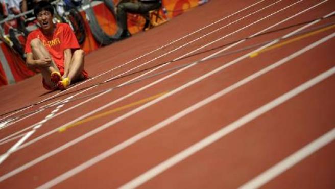 El atleta chino Liu Xiang se lamenta tras lesionarse antes del comienzo de la primera ronda de los 110 metros vallas en los Juegos de Pekín (EFE)