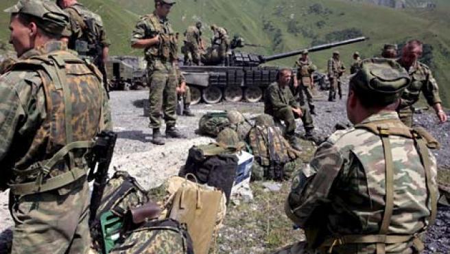 Un grupo de soldados rusos se toma un descanso en su camino de Tskhinvali a Rusia cerca de la aldea de Dzhava, en Osetia del Sur. (EFE)