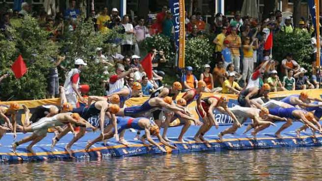 Vista general de los atletas tirándose de cabeza al lago de la Casa de Campo de Madrid para disputar la prueba de natación de la Copa del Mundo de triatlón de Madrid. (Víctor Lerena/EFE)
