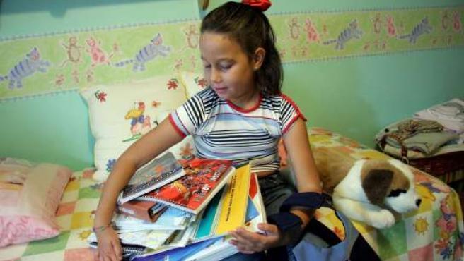Una niña sostiene sus libros de texto.