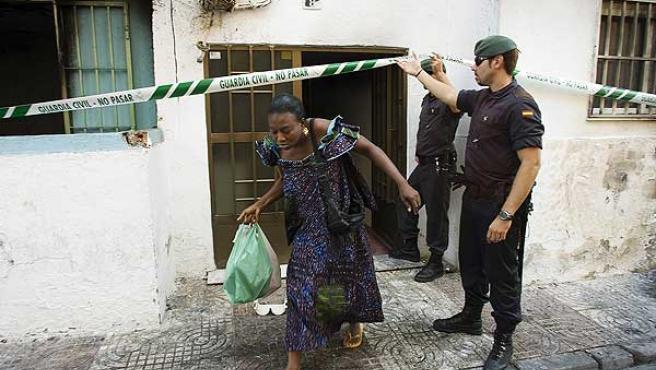 Una mujer sale de uno de los edificios incendiados en Roquetas.