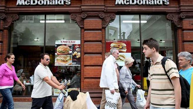 Varias personas pasan junto a un restaurante de comida rápida McDonald en las calles de Londres. (Andy Rain / EFE).