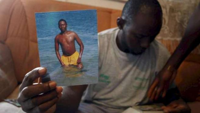 Un amigo del joven senegalés muestra la imagen del fallecido.