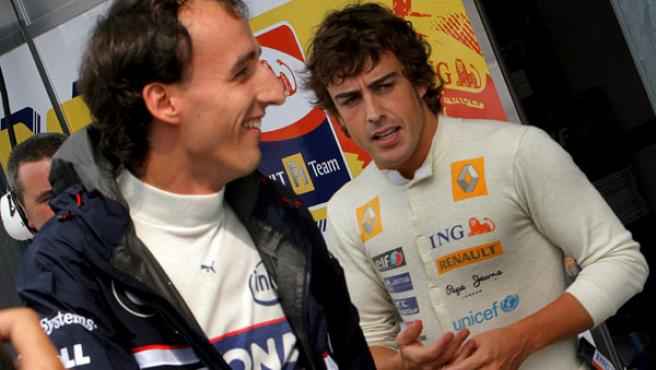 El piloto español de Fórmula Uno Fernando Alonso (dcha), del equipo Renault, charla con el polaco Robert Kubica (izda), de BMW Sauber, en el circuito de Monza. (EFE)