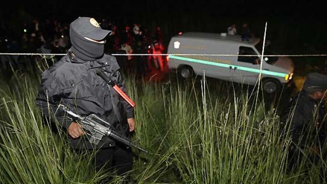 Un policía mexicano controla el perímetro de seguridad establecido en el bosque de 'La marquesa', donde se han encontrado los cuerpos de 24 personas asesinadas. (Daniel Aguilar / Reuters).