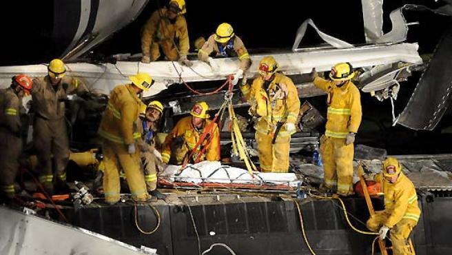 Varios miembros de los servicios de rescate evacúan el cuerpo de un policía de Los Ángeles fuera de servicio del lugar después de que tren de pasajeros y uno de mercancías chocaran en Chatsworth. (Andrew Gombert / EFE).