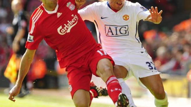 El lateral derecho del Liverpool Álvaro Arbeloa (izda.) lucha por el balón con Tévez, del Manchester United.