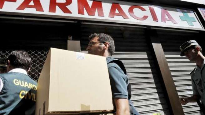 Agentes de la Guardia Civil sacan el material decomisado en una farmacia intervenida en Valencia (EFE).