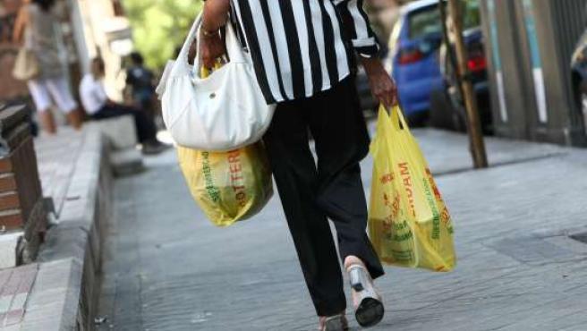 Una mujer lleva la compra en las tradicionales bolsas de plástico en una imagen de archivo.