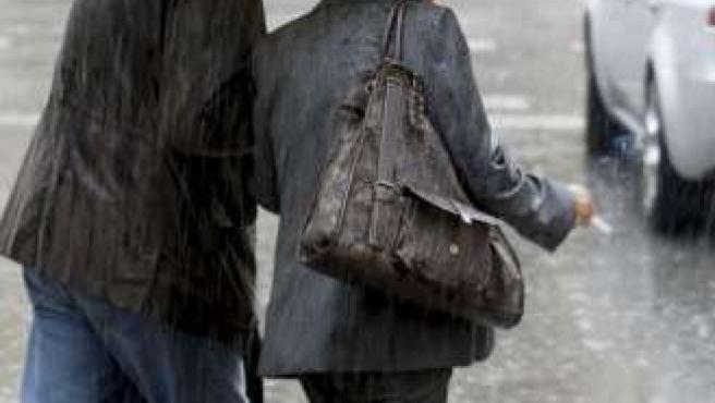 Dos viandantes se protegen de la lluvia que ha sorprendido a muchos en este inicio de otoño. (EFE)
