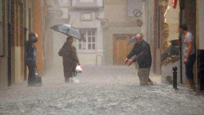 Varios vecinos asisten a la corriente de agua que pasa ante sus casas por las fuertes precipitaciones que asolan España. (ARCHIVO)