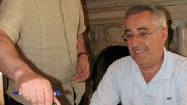 El alcalde de Alcover observa las botellas de cerveza hecha con avellanas, junto con uno de los socios de Cerveses La Gardènia. (ACN)
