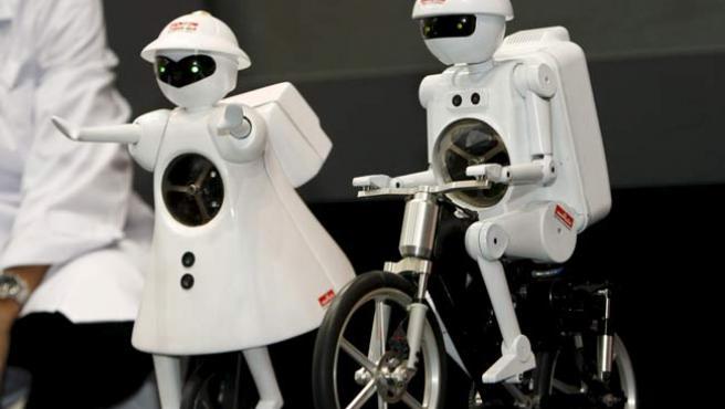 Dos robots montados en sus monociclos.