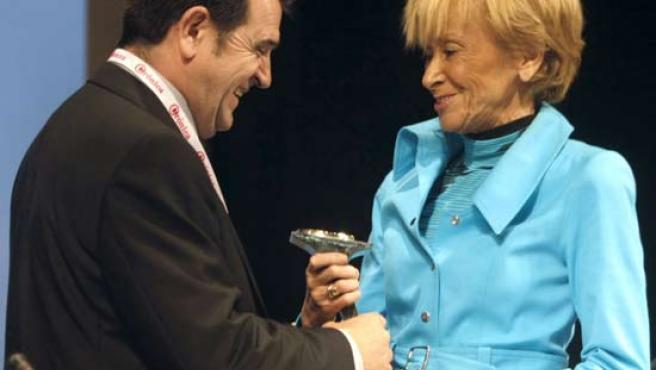 La vicepresidenta primera del Gobierno, María Teresa Fernández de la Vega recibe una estatuilla de Arsenio Escolar, presidente de la Asociación Española de Editoriales Publicaciones Periódicas (AEEPP).