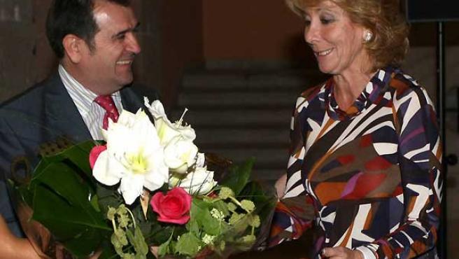 Esperanza Aguirre, recibiendo un ramo de flores junto a Arsenio Escolar. (JORGE PARÍS)