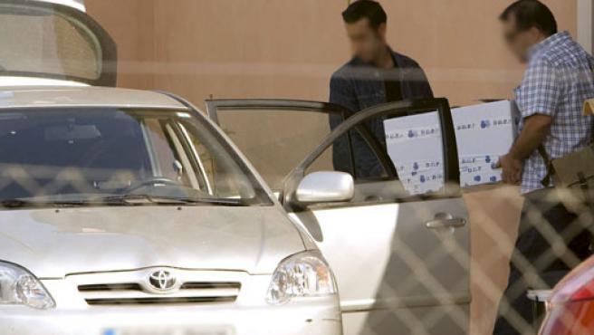 Dos policías transportan material incautado en la operación (EFE).