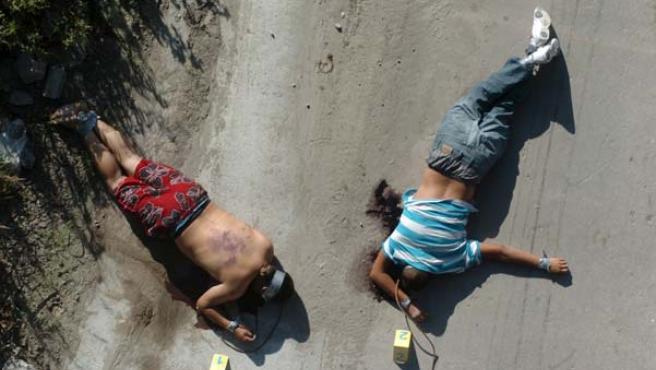 Los cuerpos de dos personas asesinadas en Tijuana en el suelo. (EFE)