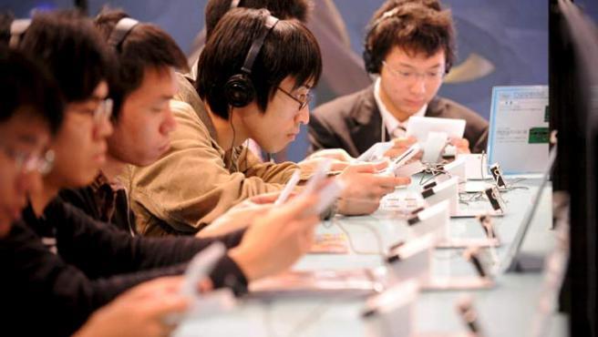 Los asistentes a la feria prueban la Nintendo DSi.