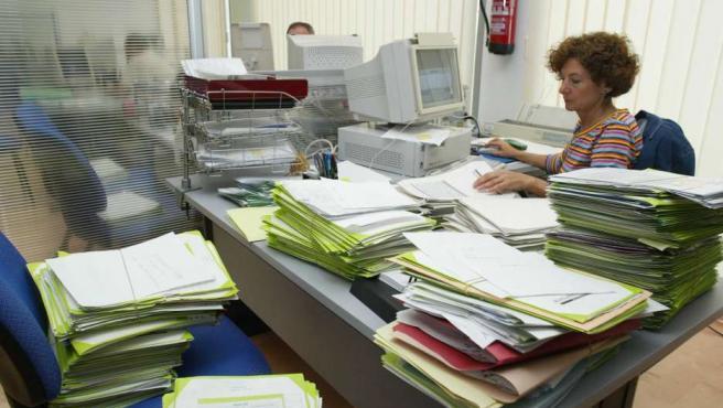Trabajadora llena de papeles en la oficina.