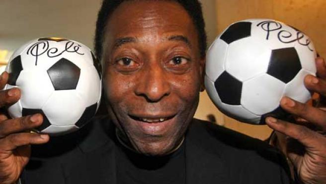 El ex futbolista brasileño Pelé posando con dos balones de fútbol en Madrid.